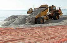 trucks dumping sand on eroding coastline